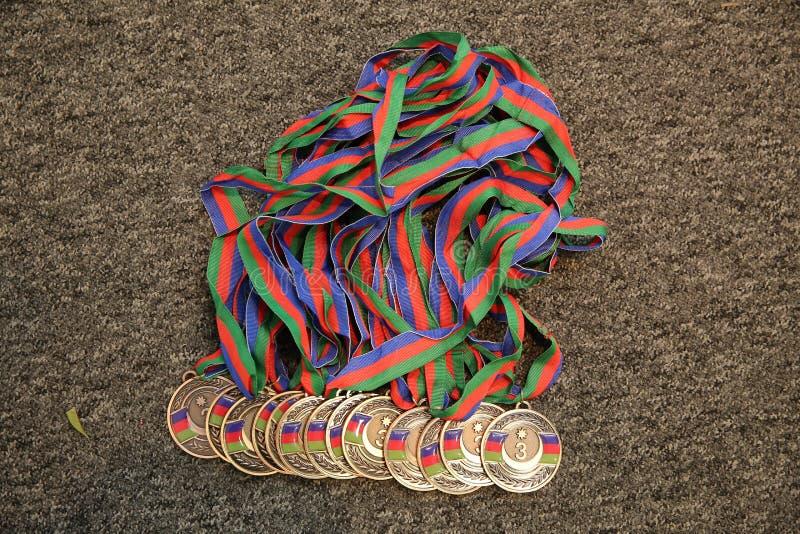 金子,与第三的奖牌 体育战利品 r 在黑背景的金牌 免版税库存图片