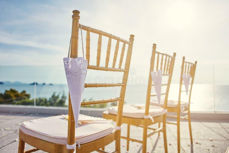 金子chiavari为有锥体的海滩婚礼地点主持玫瑰花瓣垂悬的特写镜头 库存照片