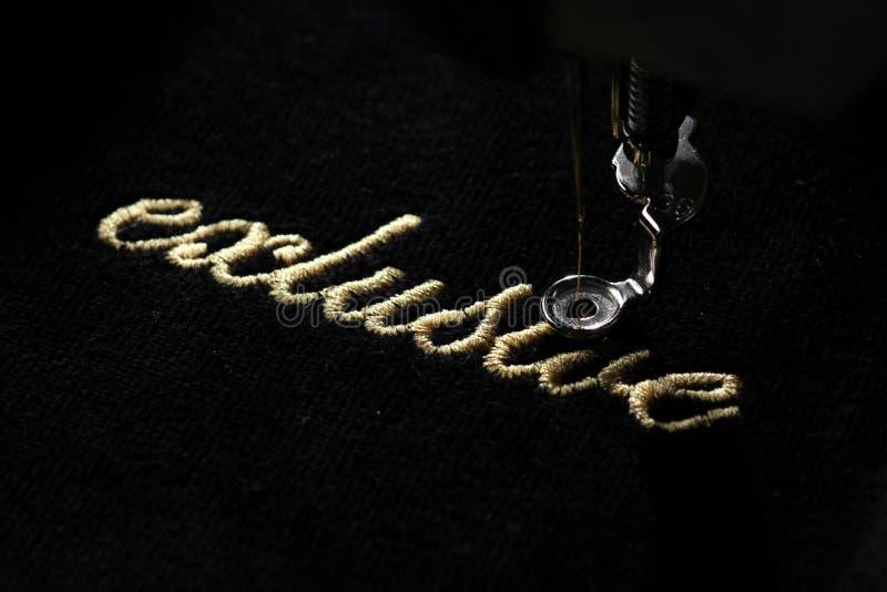 金字法& x22刺绣; exclusive& x22;在与刺绣机器的黑柔软光滑的织品 免版税库存照片