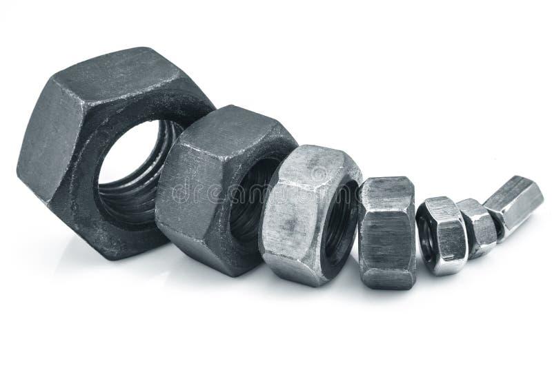 金属不同的大小六方形螺母  免版税库存照片