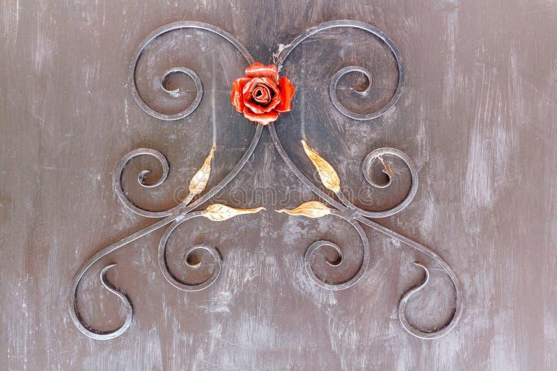 金属分支、叶子和一朵红色玫瑰的装饰装饰品 库存图片