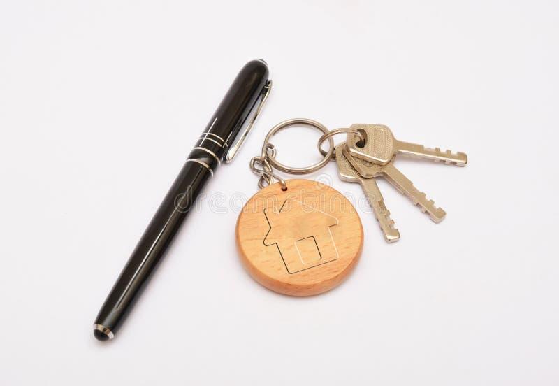 金属化与在白色背景和钥匙圈的门钥匙隔绝的笔 库存照片