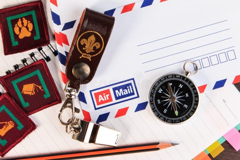 金属化与皮革钥匙链,指南针,在信封的徽章的口哨 免版税库存照片