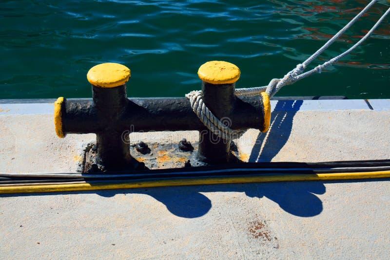 金属化在一个码头的bitt有系泊缆和一缚住的在前面 免版税库存照片
