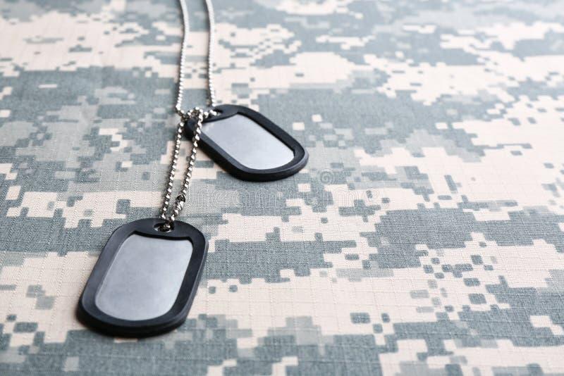 金属化在伪装背景的军事ID标记 免版税库存照片