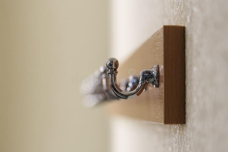 金属化在垂悬在墙壁上的一个木挂衣架特写镜头的勾子 库存图片