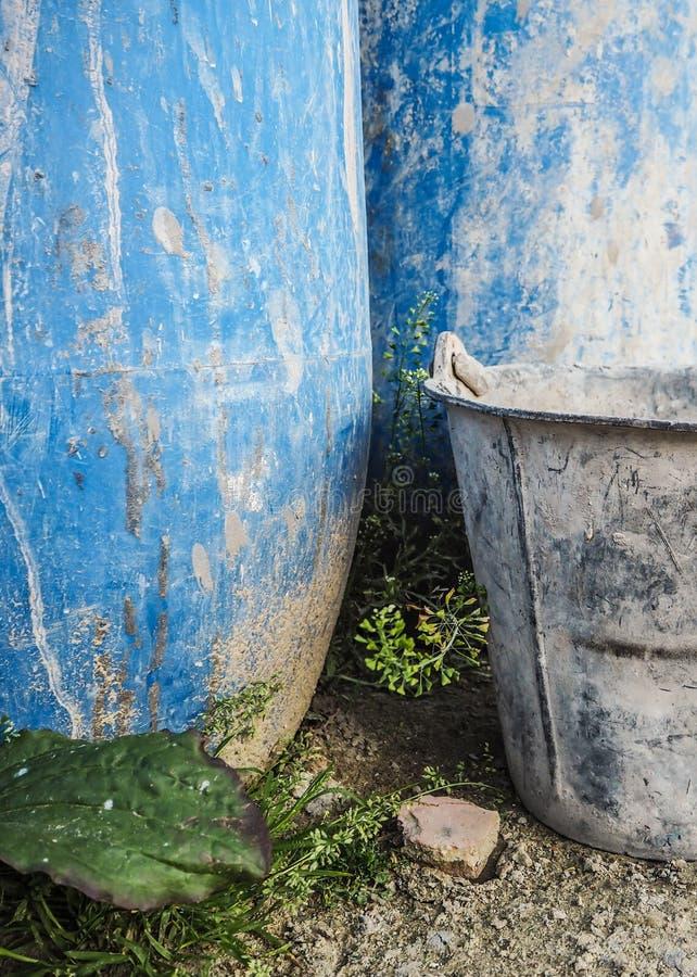 金属化在建造场所和蓝色塑料桶使用的桶 库存照片