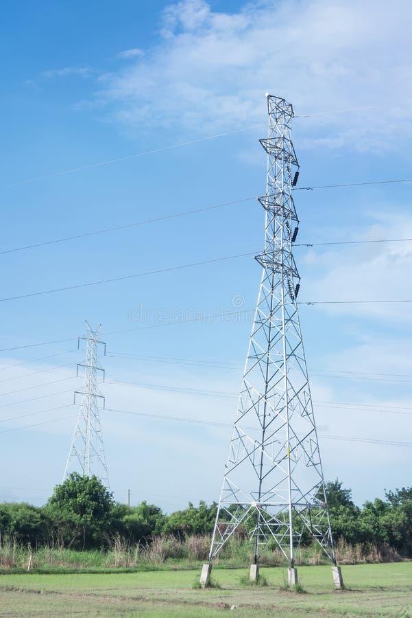 金属化在领域的电塔与蓝天 免版税图库摄影