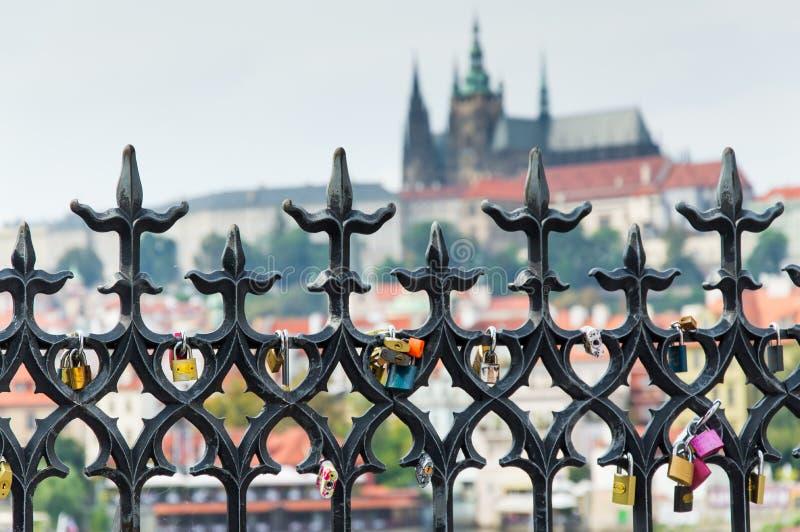 金属化有挂锁的篱芭,布拉格城堡在背景中 免版税图库摄影
