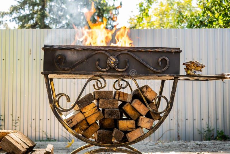 金属化格栅,伪造,手工制造,与样式 在木头的热的火与烤肉和烤产品的烟 免版税图库摄影
