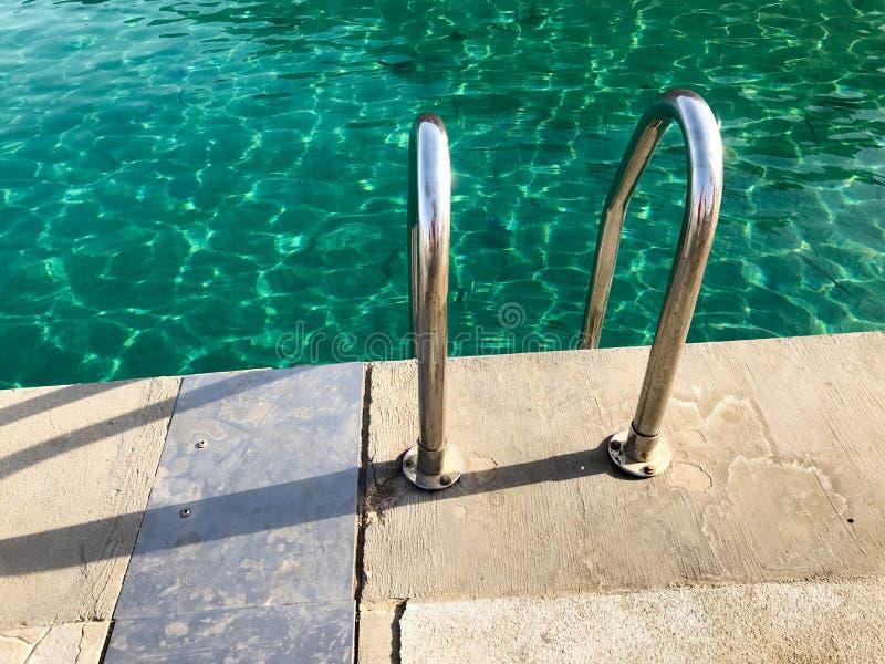 金属化镀铬物铁发光的弯曲的不锈钢扶手栏杆,台阶,下降到水池,海,在一名热带温暖的清教徒的水里 图库摄影