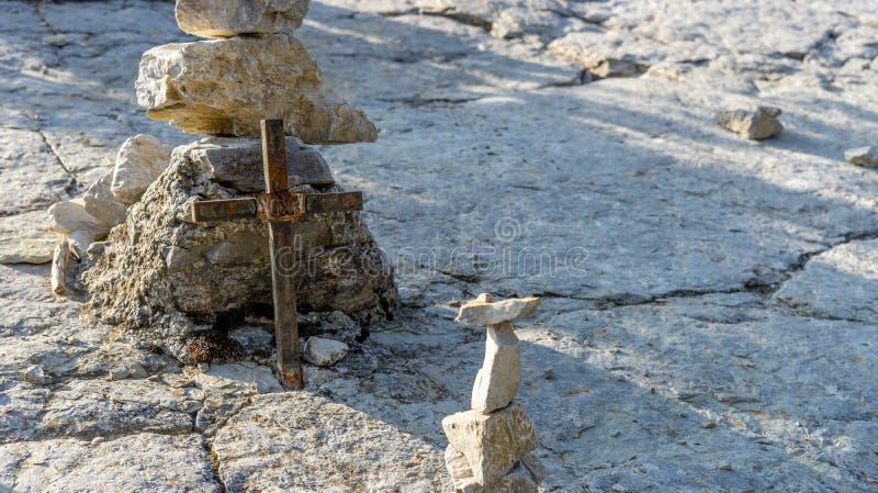 金属十字架和被堆积的石头 图库摄影
