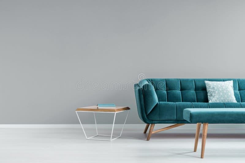 金属和木头与站立在有枕头的绿松石沙发旁边的书的茶几在灰色客厅内部真正的照片与pla的 免版税库存图片