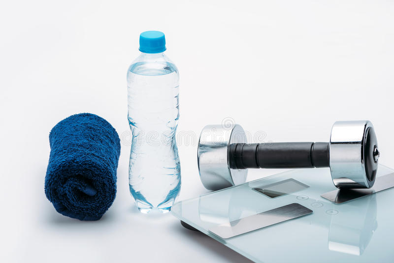 金属哑铃、标度、毛巾和瓶用在白色隔绝的水 饮料水 图库摄影