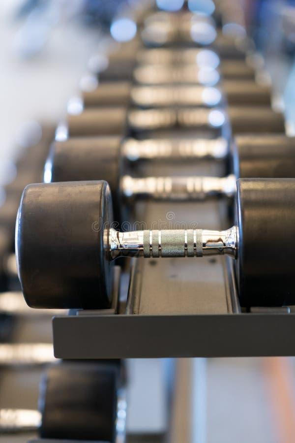 金属哑铃特写镜头行在机架的在健身房 免版税库存图片