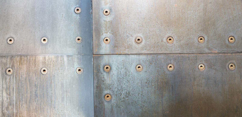 金属在墙壁上scewed的钢机器 库存图片