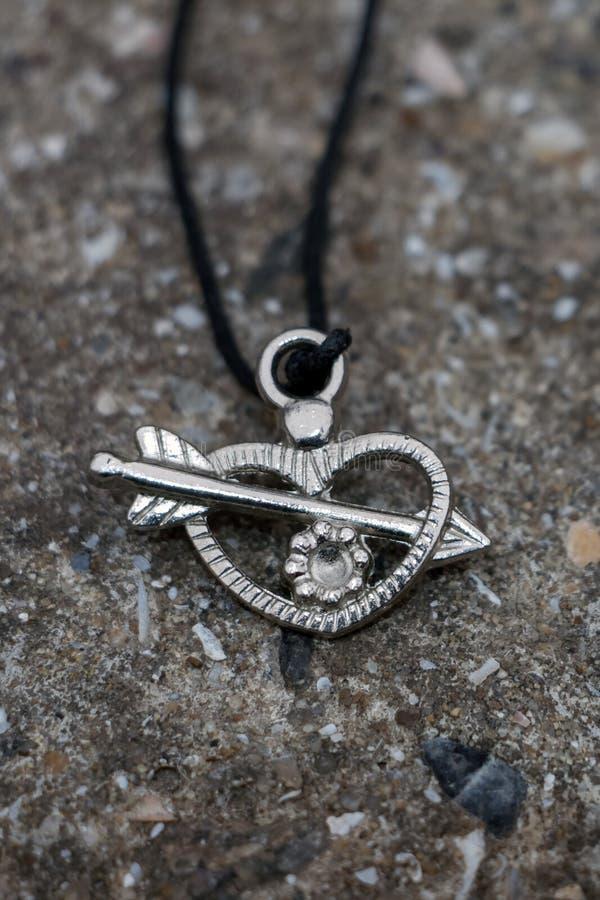 金属垂饰,忘记在石头,以心脏的形式,箭头击穿 免版税图库摄影
