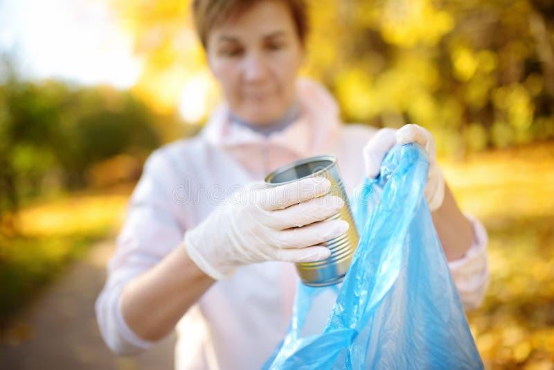 金属垃圾的志愿采摘和投入它在生物可分解的垃圾袋子在户外 库存照片