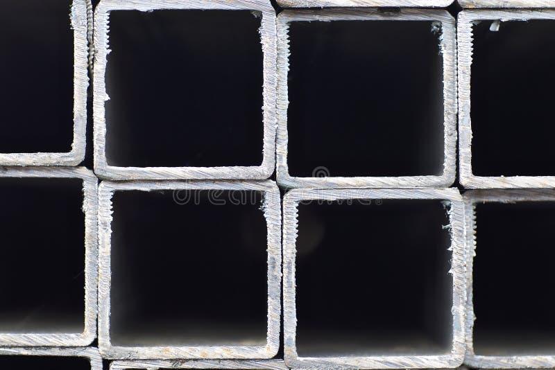 金属外形管子组装的长方形横断面在金属制品仓库  免版税库存照片