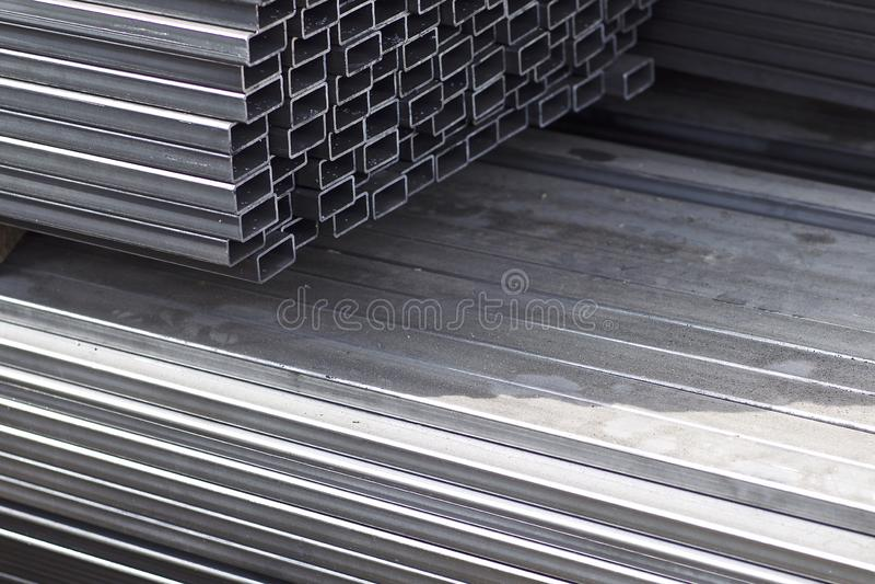 金属外形管子组装的长方形横断面在金属制品仓库  免版税图库摄影