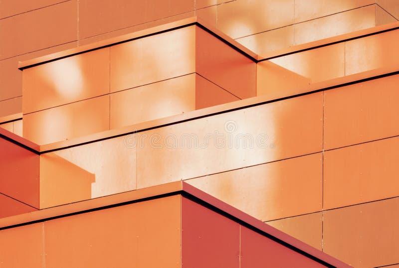 金属大厦门面桔黄色几何背景  免版税库存照片