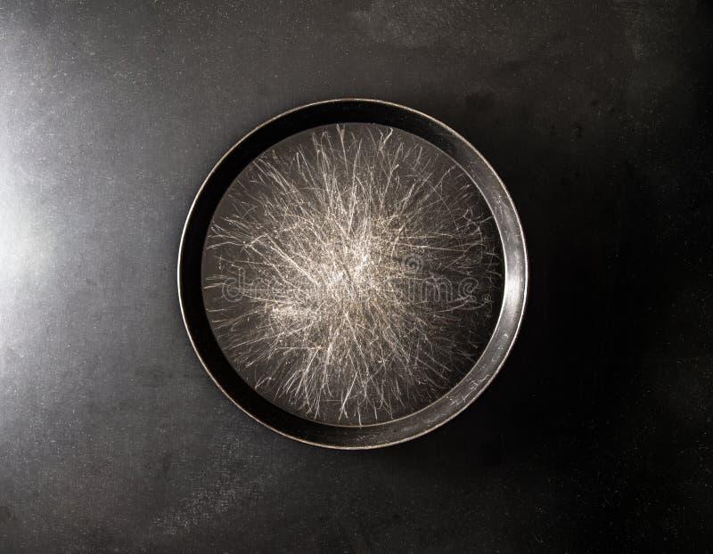 金属平底锅在黑暗的背景中 库存照片