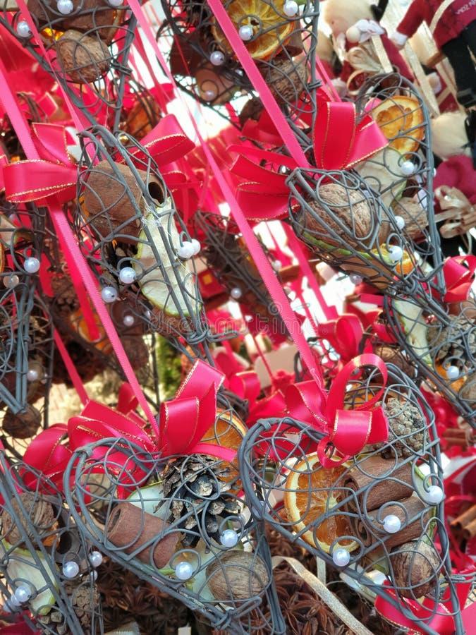 金属心脏圣诞装饰充满肉桂皮、核桃和杉木锥体 库存图片