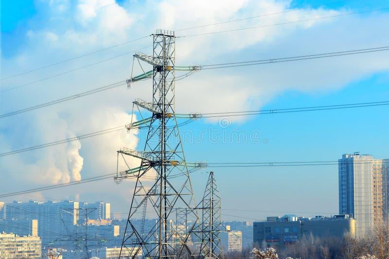 金属支持在前面的高压输电线,反对背景,在冷淡的阴霾,住宅高层建筑物 库存图片