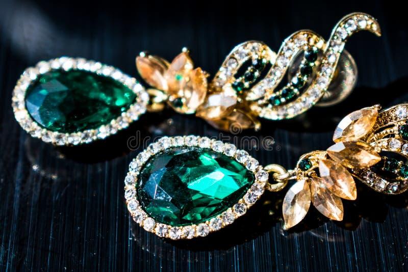 金属有绿色,鲜绿色石头,白色和黄色假钻石的金耳环 在黑光滑的背景 免版税库存图片