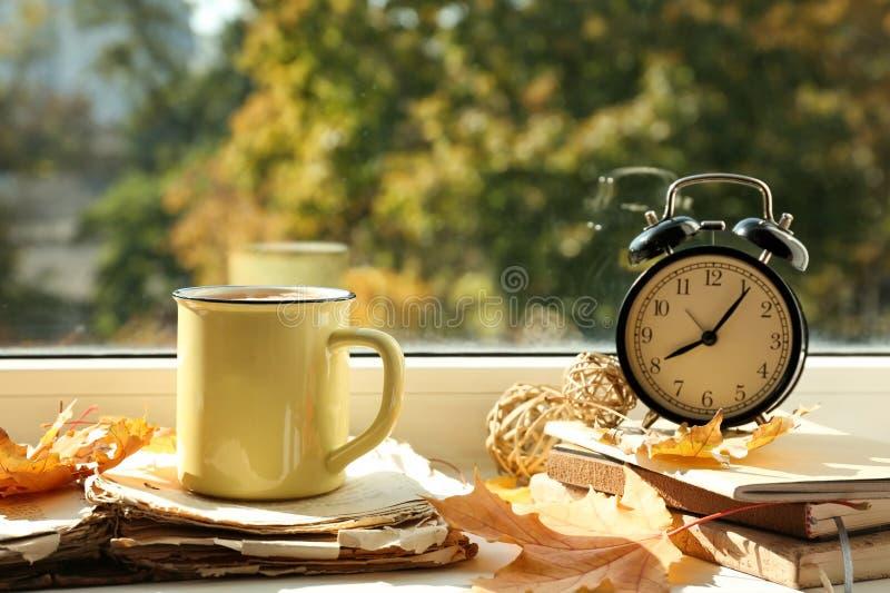 金属杯子与书和秋叶的芳香茶在窗台 库存图片
