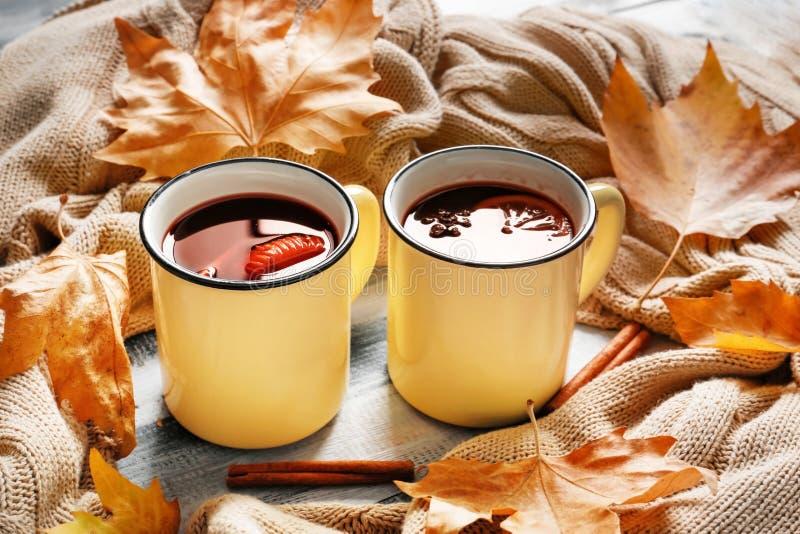 金属杯子与温暖的格子花呢披肩的可口加香料的热葡萄酒在木桌上 图库摄影