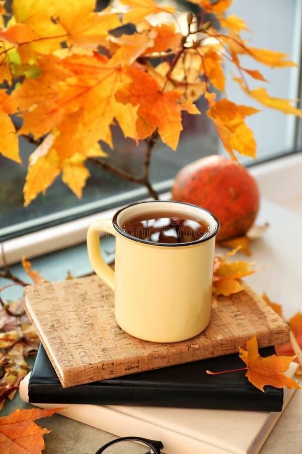 金属杯子与秋叶的芳香茶在窗台 图库摄影