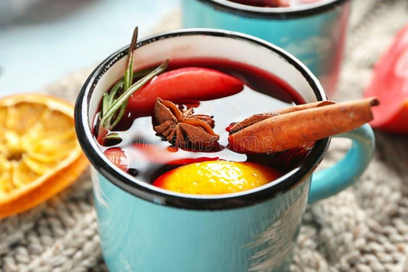 金属杯子在温暖的格子花呢披肩的可口加香料的热葡萄酒 免版税库存图片