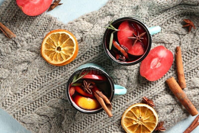 金属杯子在温暖的格子花呢披肩的可口加香料的热葡萄酒 库存图片