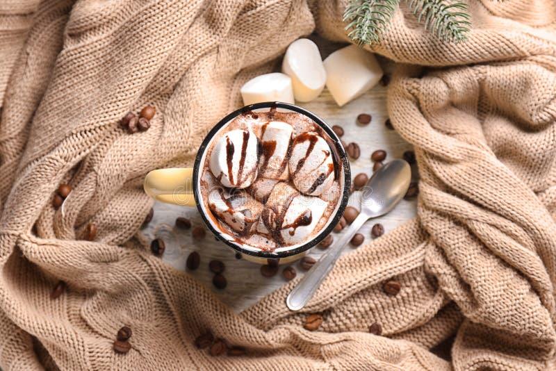 金属杯子巧克力热饮用蛋白软糖和温暖的格子花呢披肩在桌上 免版税图库摄影