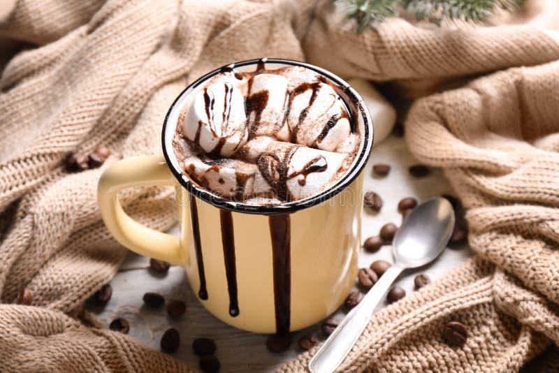 金属杯子巧克力热饮用蛋白软糖和温暖的格子花呢披肩在桌上 免版税库存图片