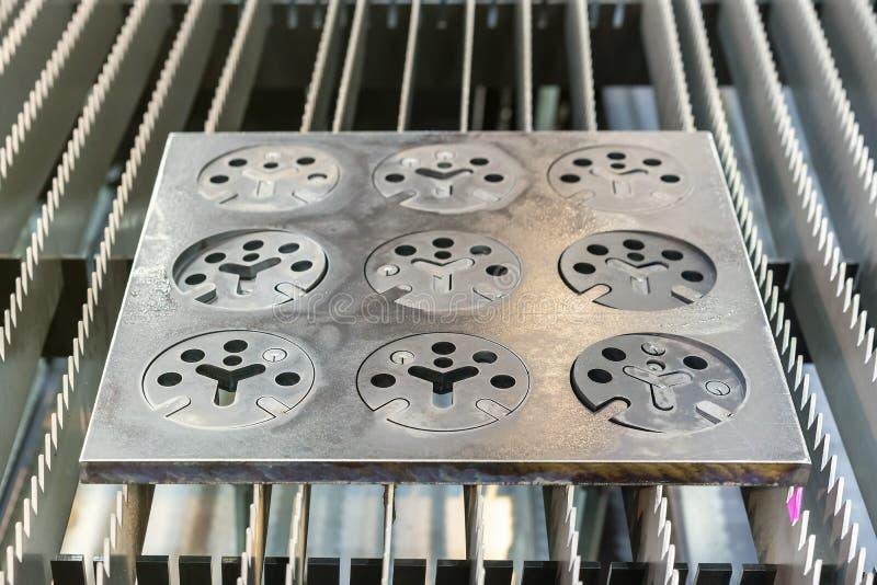 金属板或由自动和高精度激光在工业的切口过程做的板材零件在工厂 免版税库存图片