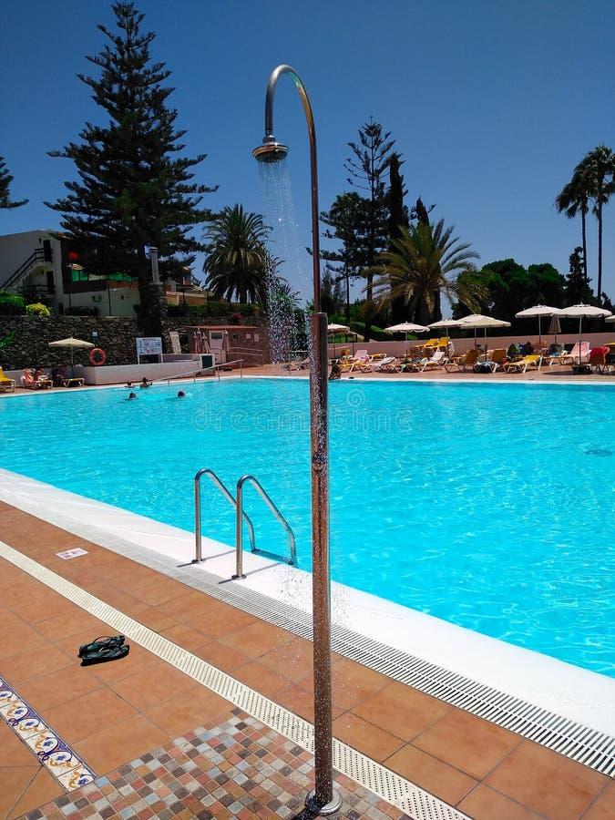 金属水阵雨下跌的下落和在一个旅游地方的游泳场后充分清楚和透明水与 免版税库存照片
