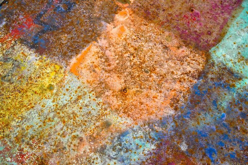金属生锈的墙壁铁的纹理绘了破旧的削皮油漆正方形,菱形,黄色,蓝色,变褐背景 免版税库存图片