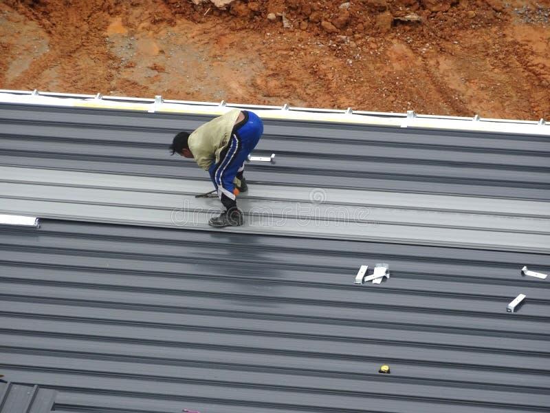 金属甲板由建筑工人的屋顶板料的设施 免版税库存图片
