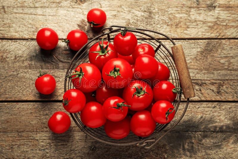 金属篮子用在木背景的新鲜的西红柿 免版税库存照片