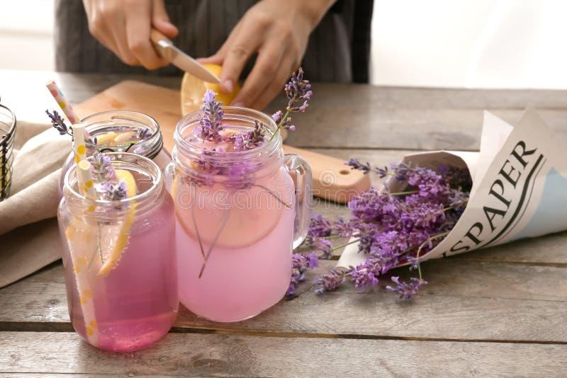 金属螺盖玻璃瓶用鲜美准备淡紫色柠檬水的饮料和年轻女人在桌上 免版税库存图片