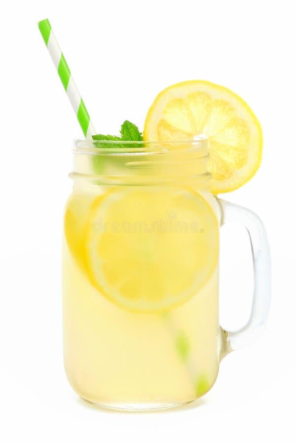 金属螺盖玻璃瓶与在白色隔绝的秸杆的柠檬水 图库摄影