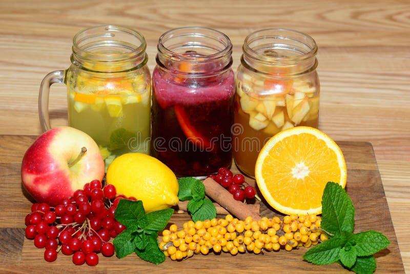 金属螺盖玻璃瓶用热的饮料填装了用莓果和果子在一张木桌上 库存照片