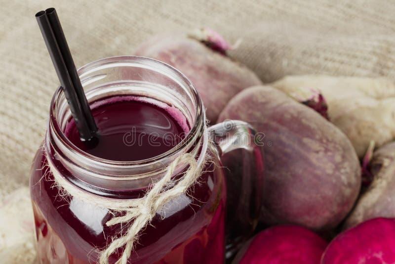 金属螺盖玻璃瓶的一张顶视图新近地被紧压的甜菜根喝和在织品的一些棵甜菜 素食主义者饮食的成份 库存照片