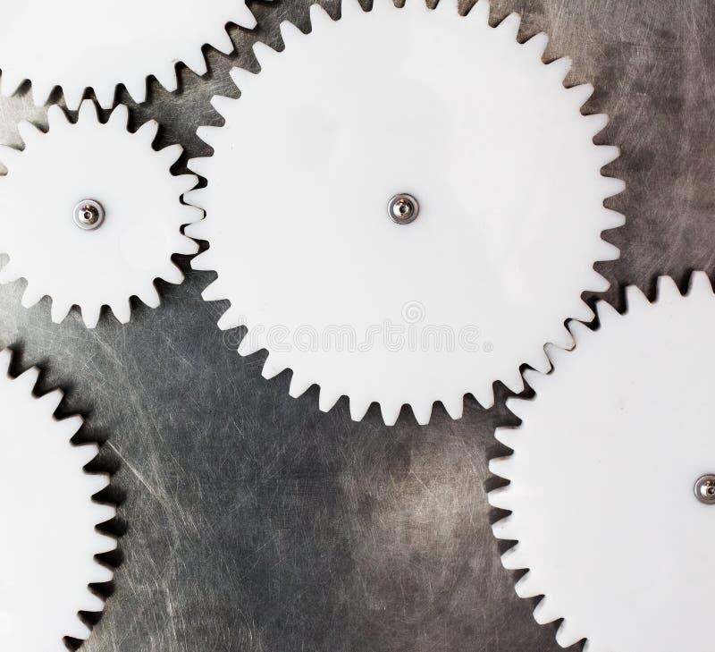 金属表面上的白色塑料齿轮 库存照片