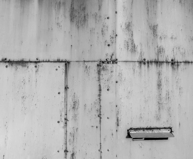 金属被缝的板料在一个车库的门的在一种中立颜色的 库存图片