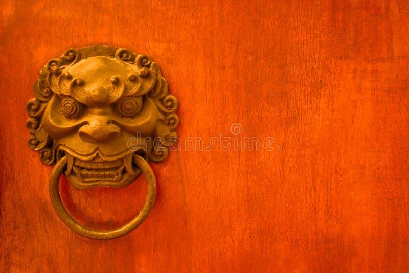 金属邪恶的面孔拉扯门和坚硬木表面背景 免版税库存照片