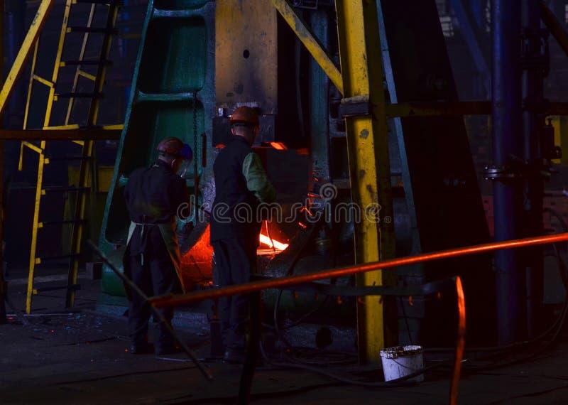 金属锻件,伪造商店 水力锤子塑造炽热宿营 免版税库存照片