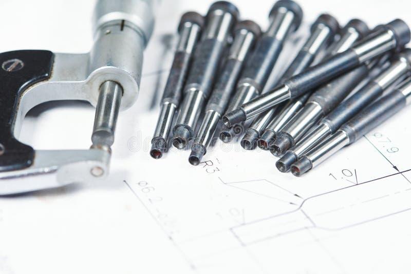 金属零件加工 与测量的测微表的细节在印刷品图画 免版税库存照片
